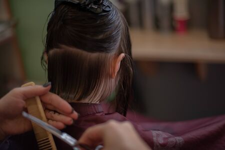 Stylist hairdresser makes a hairstyle for a cute little girl in a beauty salon.Hairdressing, hair cutting.A girl is given the length of her hair in a beauty salon.A series of photos is a haircut