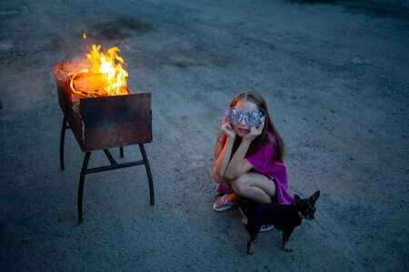 girls wearing glasses.Halloween concept.A girl of 9-10 years old wore glasses with a spider design for Halloween or a theme party.School girl in pink t-shirt in the evening light waiting for Halloween