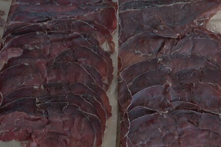 Sliced cured bresaola. Bresaola - Italian beef jerky. Sliced beef bresaol. Italian appetizer, which in the classic version is lean beef salted in a dry way. basturma.Bresaola is a delicious appetizer