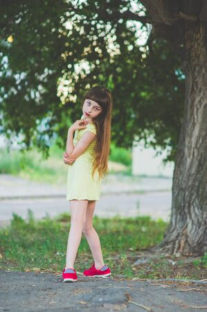 Girl walks in the woods. Girl walking in the park.A little girl of 9 years went for a walk on the street in summer or early autumn. Schoolgirl walking after school. Girl with long hair in a dress 写真素材 - 132265392