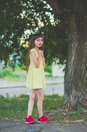 Girl walks in the woods. Girl walking in the park.A little girl of 9 years went for a walk on the street in summer or early autumn. Schoolgirl walking after school. Girl with long hair in a dress 写真素材 - 132266002
