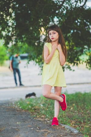 Girl walks in the woods. Girl walking in the park.A little girl of 9 years went for a walk on the street in summer or early autumn. Schoolgirl walking after school. Girl with long hair in a dress 写真素材 - 132265971