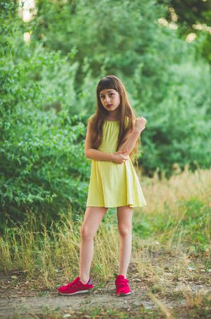 Girl walks in the woods. Girl walking in the park.A little girl of 9 years went for a walk on the street in summer or early autumn. Schoolgirl walking after school. Girl with long hair in a dress 写真素材 - 132268063