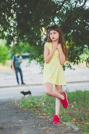 Girl walks in the woods. Girl walking in the park.A little girl of 9 years went for a walk on the street in summer or early autumn. Schoolgirl walking after school. Girl with long hair in a dress 写真素材 - 132265961