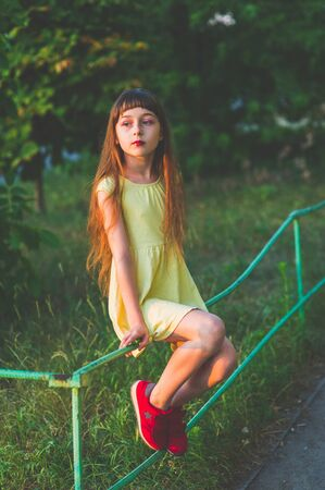 Girl walks in the woods. Girl walking in the park.A little girl of 9 years went for a walk on the street in summer or early autumn. Schoolgirl walking after school. Girl with long hair in a dress 写真素材 - 132266044