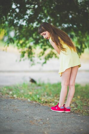 Girl walks in the woods. Girl walking in the park.A little girl of 9 years went for a walk on the street in summer or early autumn. Schoolgirl walking after school. Girl with long hair in a dress 写真素材 - 132265443