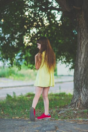 Girl walks in the woods. Girl walking in the park.A little girl of 9 years went for a walk on the street in summer or early autumn. Schoolgirl walking after school. Girl with long hair in a dress 写真素材 - 132265860