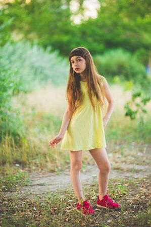 Girl walks in the woods. Girl walking in the park.A little girl of 9 years went for a walk on the street in summer or early autumn. Schoolgirl walking after school. Girl with long hair in a dress 写真素材 - 132268359
