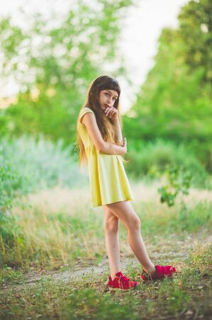 Girl walks in the woods. Girl walking in the park.A little girl of 9 years went for a walk on the street in summer or early autumn. Schoolgirl walking after school. Girl with long hair in a dress 写真素材 - 132268284