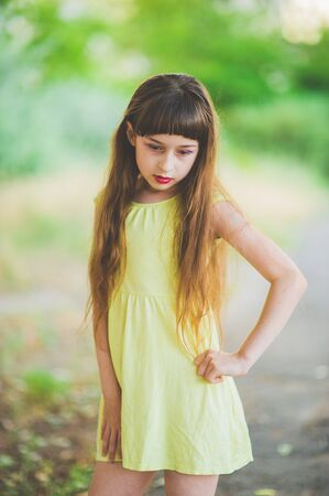 Girl walks in the woods. Girl walking in the park.A little girl of 9 years went for a walk on the street in summer or early autumn. Schoolgirl walking after school. Girl with long hair in a dress 写真素材 - 132268331
