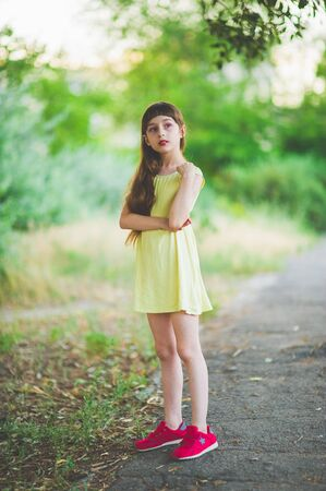Girl walks in the woods. Girl walking in the park.A little girl of 9 years went for a walk on the street in summer or early autumn. Schoolgirl walking after school. Girl with long hair in a dress 写真素材 - 132268262