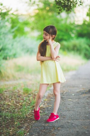 Girl walks in the woods. Girl walking in the park.A little girl of 9 years went for a walk on the street in summer or early autumn. Schoolgirl walking after school. Girl with long hair in a dress 写真素材 - 132265937