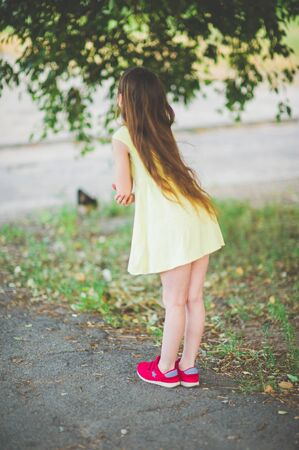 Girl walks in the woods. Girl walking in the park.A little girl of 9 years went for a walk on the street in summer or early autumn. Schoolgirl walking after school. Girl with long hair in a dress 写真素材 - 132143266