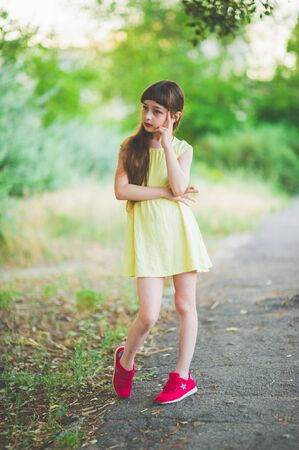 Girl walks in the woods. Girl walking in the park.A little girl of 9 years went for a walk on the street in summer or early autumn. Schoolgirl walking after school. Girl with long hair in a dress 写真素材 - 132266078