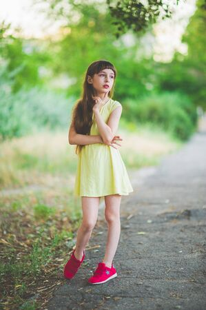 Girl walks in the woods. Girl walking in the park.A little girl of 9 years went for a walk on the street in summer or early autumn. Schoolgirl walking after school. Girl with long hair in a dress