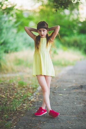Girl walks in the woods. Girl walking in the park.A little girl of 9 years went for a walk on the street in summer or early autumn. Schoolgirl walking after school. Girl with long hair in a dress 写真素材 - 132268091