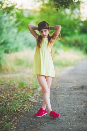 Girl walks in the woods. Girl walking in the park.A little girl of 9 years went for a walk on the street in summer or early autumn. Schoolgirl walking after school. Girl with long hair in a dress 写真素材 - 132268370