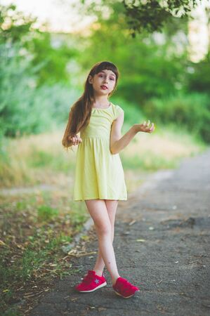Girl walks in the woods. Girl walking in the park.A little girl of 9 years went for a walk on the street in summer or early autumn. Schoolgirl walking after school. Girl with long hair in a dress 写真素材 - 132268599