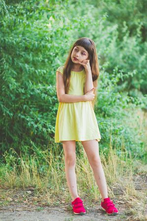 Girl walks in the woods. Girl walking in the park.A little girl of 9 years went for a walk on the street in summer or early autumn. Schoolgirl walking after school. Girl with long hair in a dress 写真素材 - 132268350