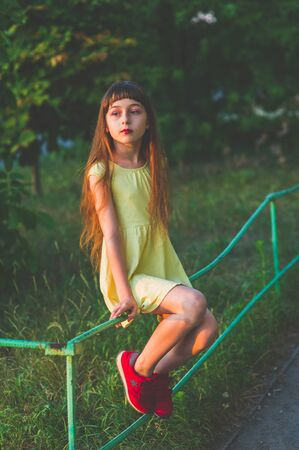 Girl walks in the woods. Girl walking in the park.A little girl of 9 years went for a walk on the street in summer or early autumn. Schoolgirl walking after school. Girl with long hair in a dress 写真素材 - 132268777