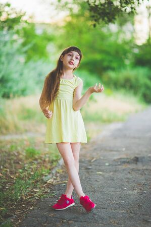 Girl walks in the woods. Girl walking in the park.A little girl of 9 years went for a walk on the street in summer or early autumn. Schoolgirl walking after school. Girl with long hair in a dress 写真素材 - 132268382