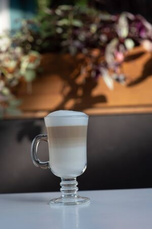 Coffee Latte Macchiato. Cup of latte in a cafe. Coffee in a glass cup shot in a cafe in the daylight. An invigorating caffeinated latte or make-up drink or cappuccino. Coffee on a table with milk foam