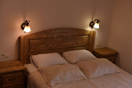 Bed in a hotel room. Bed and pillows. A bed with a wooden headboard and two cabinets and floor lamps. Day or evening hotel. Place for sleeping and relaxing. Rectangular pillows in a white pillowcase Stock fotó