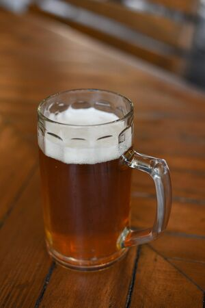Glass of beer on wooden table. Beer in a glass. Beer in a glass at a pub