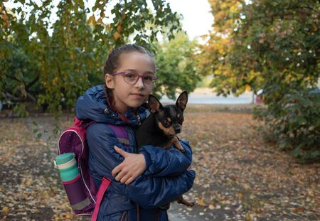 Serious teen schoolgirl with backpack, hands crossed, outdoor. Schoolgirl in a jacket and with a backpack. A girl of 9-10 years old goes to school in the fall. School backpack with a bottle of water.