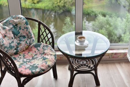 Cup of coffee on a glass table by the window and an armchair.Table, chair, cups and ashtray on hotels balcony. A glass table and an armchair is a place for relaxation and coffee. Food photography Stock fotó