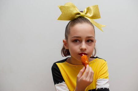 Young cheerleader. Athlete cheerleader eats after the performance. A 9-year-old girl eats deep-fried cheese and crab legs. The girl is having lunch. Hungry child after or before exercise