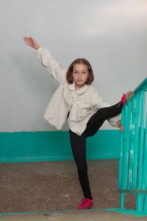 European sporty girl in casual clothes showing vertical twine outdoor. Stretching training. Little girl doing twine stretching. The girl decided to make a stretch at the entrance to her house