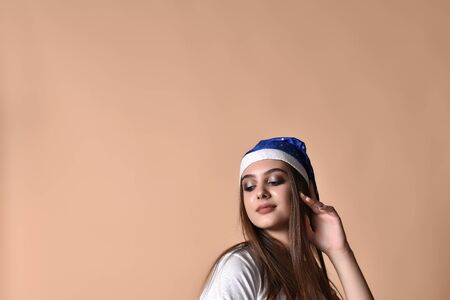Young girl in santa claus hat posing in studio on a beige background.