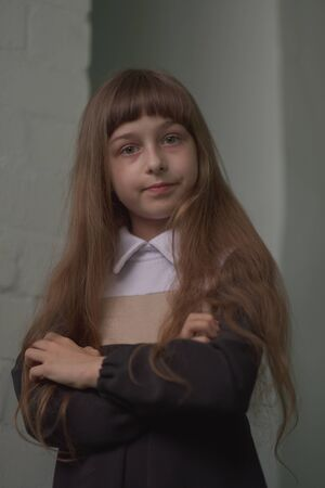 Little girl schoolgirl stands. Child 9 years old schoolgirl in a school dress with brown hair.Schoolgirl is looking at the camera. Long hair in a girl. Child on a background of a white brick wall. Stockfoto