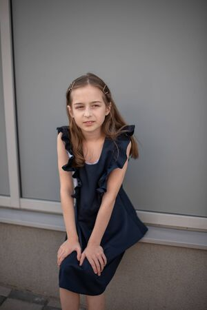 Schoolgirl in a blue dress posing on the street. A girl with blond hair 9-19 years old. Soon to school. Girl in a school dark blue dress. Beautiful young girl in vintage dress posing outdoors