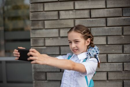 Smiling beatiful preteen girl taking a selfie outdoors. Child taking a self portrait with mobile phone. technology and communication concept. Schoolgirl take selfie on the street. Back to school