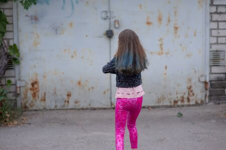Portrait of nine year old girl. The child is walking in the fresh air. Teenager with blue strands on her hair. The girl with brown hair. A series of photos of a girl of 8 or 9 years old Фото со стока