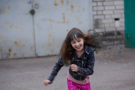 Portrait of nine year old girl. The child is walking in the fresh air. Teenager with blue strands on her hair. The girl with brown hair. A series of photos of a girl of 8 or 9 years old Reklamní fotografie