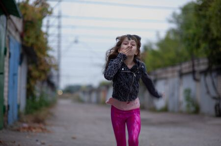 Portrait of nine year old girl. The child is walking in the fresh air. Teenager with blue strands on her hair. The girl with brown hair. A series of photos of a girl of 8 or 9 years old Stock fotó