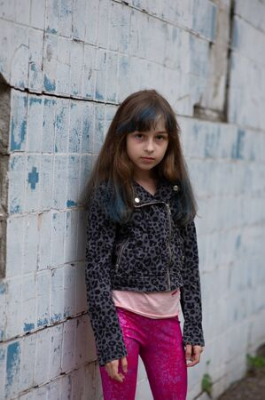 Portrait of nine year old girl. The child is walking in the fresh air. Teenager with blue strands on her hair. The girl with brown hair. A series of photos of a girl of 8 or 9 years old Stock Photo