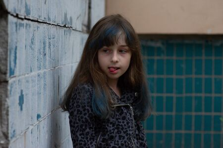 Portrait of nine year old girl. The child is walking in the fresh air. Teenager with blue strands on her hair. The girl with brown hair. A series of photos of a girl of 8 or 9 years old Banco de Imagens