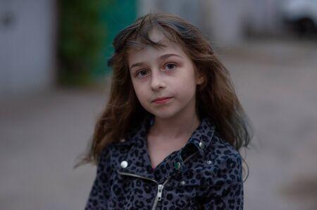 Portrait d'une fillette de neuf ans. L'enfant marche au grand air. Adolescente avec des mèches bleues sur ses cheveux. La fille aux cheveux bruns. Une série de photos d'une fille de 8 ou 9 ans