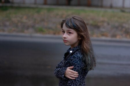 Portrait of nine year old girl. The child is walking in the fresh air. Teenager with blue strands on her hair. The girl with brown hair. A series of photos of a girl of 8 or 9 years old