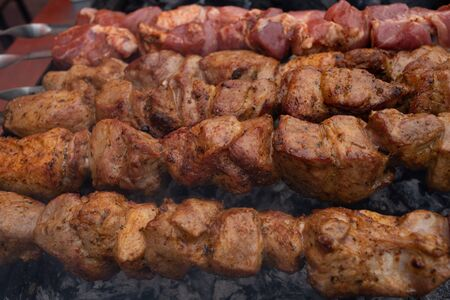 Grilled kebab cooking on metal skewer. Roasted meat cooked at barbecue. BBQ fresh beef meat chop slices. Traditional eastern dish, shish kebab. skewers on skewers.Roasted meat cooked at barbecue.BBQ Stock Photo