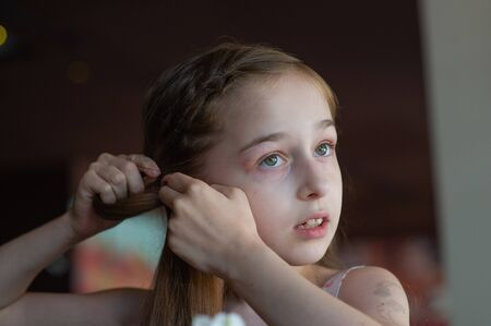 Portrait of a 9 years old female child, portrait concept of a child. Close-up face of beautiful girl 8-9 years old. Concept child teenager. A girl with long blond hair. Girl 9 years old in a cafe