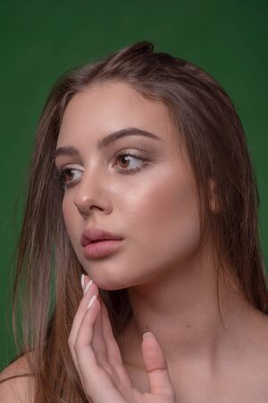 Beautiful girl with classic make up, on a bright background. Beauty face. Photo taken in the studio. Beauty photo girl on a green background. Girl with puffy natural lips and brown hair. Portrait
