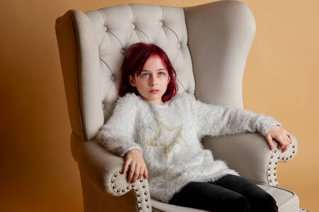 beautiful girl 9 years old. Girl 9 years old in a chair in the studio. A teenager with red hair in a beige warm fluffy sweater sits comfortably in a gray robe. A haircut girl on a beige background Stock fotó