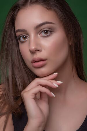 Beautiful girl with classic make up, on a bright background. Beauty face. Photo taken in the studio. Beauty photo girl on a green background. Girl with puffy natural lips and brown hair. Portrait Stock fotó - 138273412