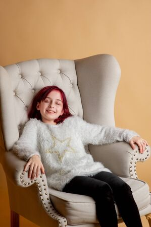 beautiful girl 9 years old. Girl 9 years old in a chair in the studio. A teenager with red hair in a beige warm fluffy sweater sits comfortably in a gray robe. A haircut girl on a beige background 写真素材