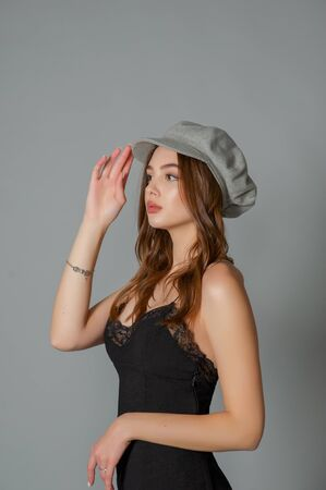 Glamorous young woman wears fashionable dress posing with fluttering hair at grey wall. Girl put forward hand in a black dress and a gray cap. Beautiful young girl with brown curly hairs. portrait